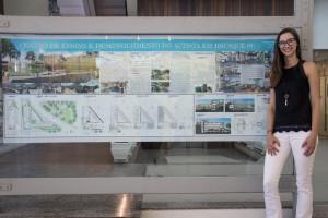 """Fotografia colorida em ambiente fechado. Hall da reitoria. A estudante Manoela Fischer posa ao lado da prancha com o projeto arquitetônico do seu TCC, em que se lê, no topo, """"Centro de Ensino e Desenvolvimento do Autista em Brusque-SC""""."""
